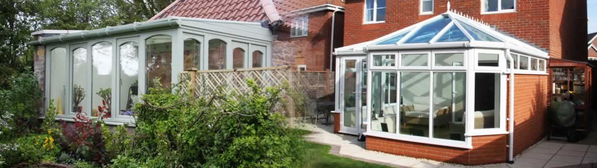One white uPVC conservatory and one green timber conservatory