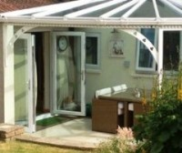 French doors leading to covered patio garden area by Mendip Conservatories
