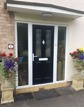 Black composite front door with side lights and flowerpots